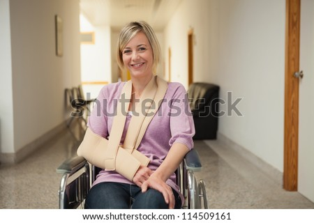 Patient in wheelchair with arm in sling in hospital corridor - stock photo