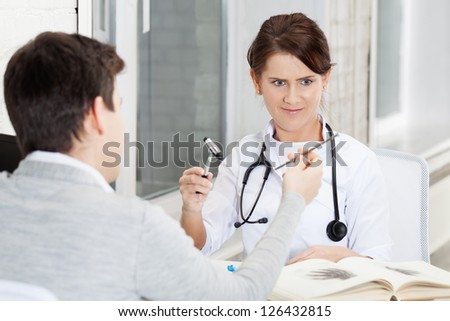 Patient joshing doctor with nail - stock photo
