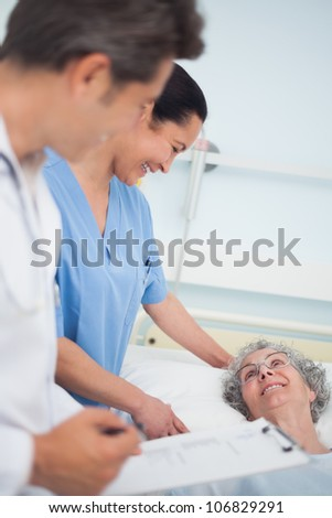 Patient laughing with a nurse and a doctor in hospital ward - stock photo