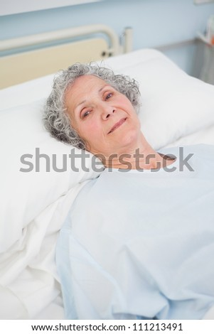 Patient looking at camera on a bed in hospital ward