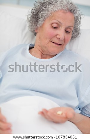 Patient looking at drugs in her hand in hospital ward - stock photo