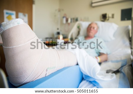 patient lying in hospital bed with broken leg bone wrapped in ca