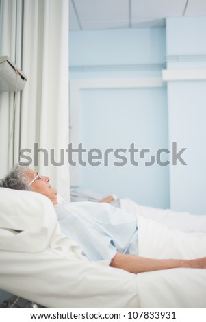 Patient lying on a medical bed in hospital ward - stock photo