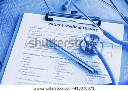 Patient medical history on a clipboard with stethoscope and a blue ballpoint pen, putting on a physician's wooden table. Blank form waiting to be filled and reviewed / examined by clinical assistant.