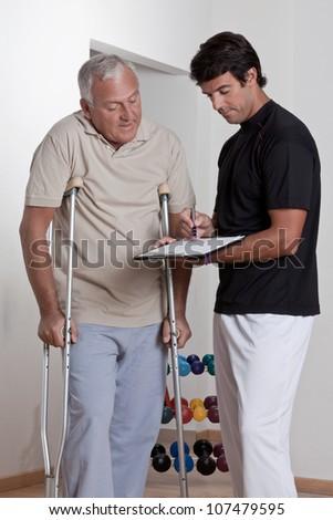 Patient on crutches discusses his progress. - stock photo