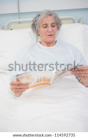 Patient reading a magazine on her bed in hospital ward - stock photo