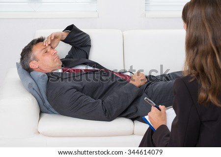 Patient Relaxing On Couch In Front Of A Female Psychiatrist With Clipboard
