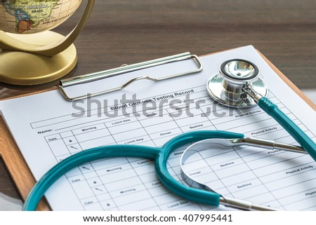 Patient's blood glucose record clip pad with doctor's stethoscope on work table/ desk: Physician note on empty paperwork in hospital/ clinic interior room: World health/ diabetes check concept    - stock photo