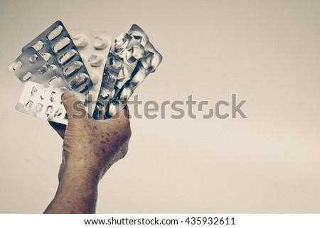 Patient's hand holding a collection of used drug tablets covers in vintage tone - Drug overuse - drug abuse concept - stock photo