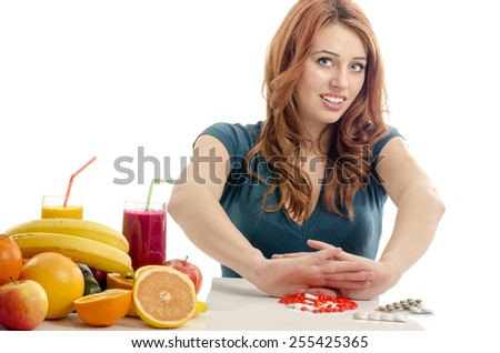 Patient saying no to medical treatment. Beautiful woman refuses to take pills and choose to eat organic raw fruits, salad, smoothie, juices for a healthy life - stock photo