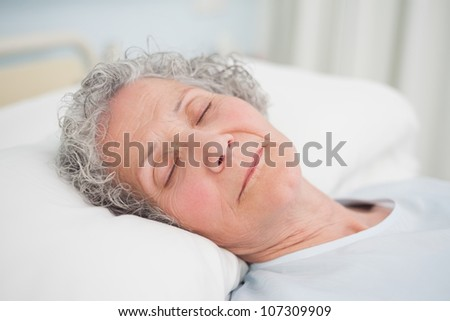 Patient sleeping on a medical bed in hospital ward - stock photo
