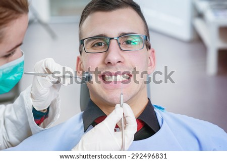 Patient smiling at dentist office. Doctor examining a patient.  - stock photo