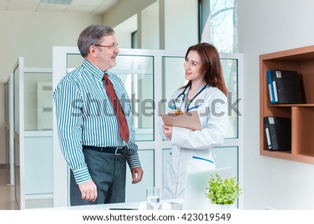 patient smiling to his doctor in medical office