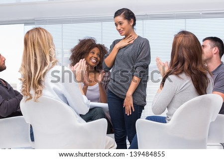Patient standing and telling her problems to therapy group - stock photo