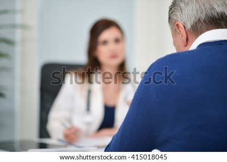 Patient talking to his doctor during a visit - stock photo
