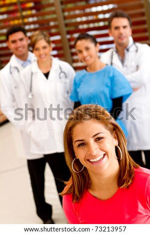Patient with a group of doctors at the background - stock photo