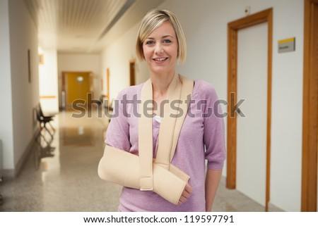 Patient with broken arm in sling in hospital corridor - stock photo