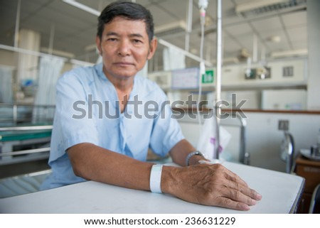 Patient with IV drip and hand tag in a hospital