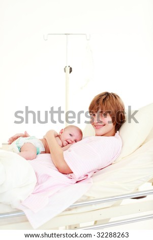 Patient with newborn baby in bed in hospital with copy-space - stock photo