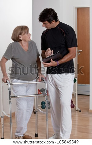 Patient with walker discusses his progress. - stock photo