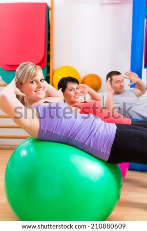 Patients at the physiotherapy doing physical exercises with therapist on training balls - stock photo