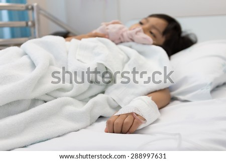 Patients hands of a girl lying on a hospital bed,dept of field - stock photo