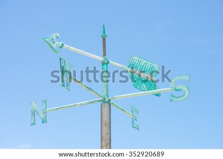 Patina green rusty old weather vane isolated on summer sunny blue sky background, with pointing arrow and symbols for orientation, copy space. - stock photo