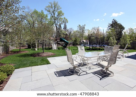Patio and back yard with playground equipment - stock photo