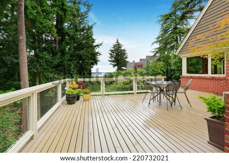 Patio and sitting area on spacious walkout deck overlooking bay - stock photo