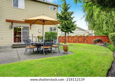 Patio area with table set and umbrella. Backyard landscape - stock photo