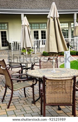 Patio furniture with tables chairs and umbrellas - stock photo
