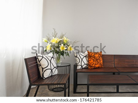 Patio lounge with garden bench and flower decoration - stock photo