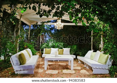patio romantic in the evening with benches and pillows chandelier and table - stock photo