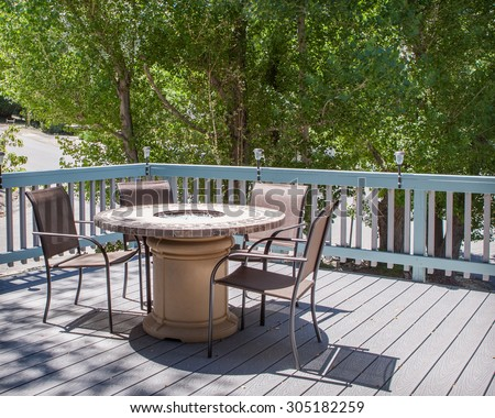 patio table with fire pit and chairs on deck - stock photo