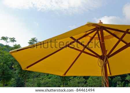 Patio umbrella with blue sky and tree background - stock photo