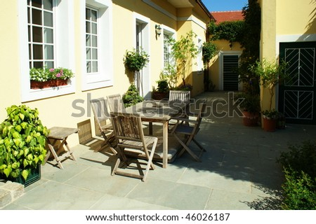 Patio with table and cane chair in a backyard