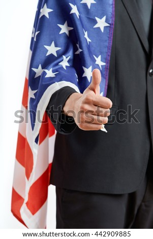 Patriotic businessman in suit covered by National American flag showing thumb up sign with his hand
