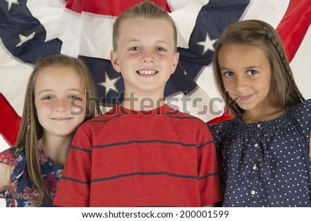 Patriotic children in front of flag banner - stock photo
