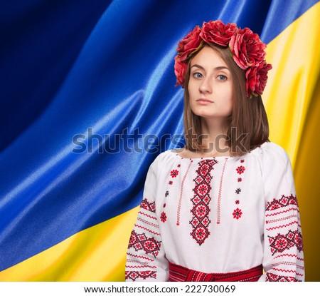 Patriotic concept.  Beautiful girl in the Ukrainian national suit against Ukrainian flag background - stock photo