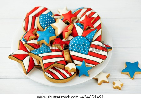 Patriotic cookies for 4th of July on a white wooden background in a white plate. With scattered stars. - stock photo