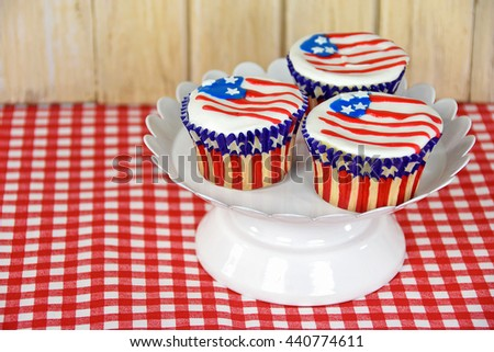 patriotic cupcakes on white pedestal plate with American flag frosting on red and white checkered fabric - stock photo