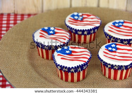 Patriotic cupcakes with flag design frosting on brown burlap plate - stock photo