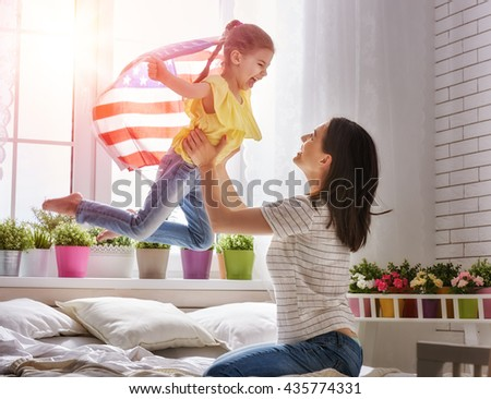 Patriotic holiday. Happy family, mother and her daughter child girl with American flag at home. USA celebrate 4th of July. - stock photo