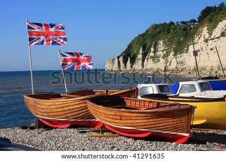 Patriotic row boats with Union Jack flags fluttering in the wind available for hire on a Devon beach - stock photo