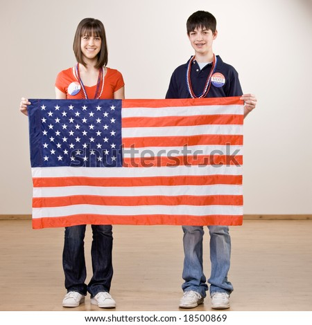 Patriotic teenagers holding up American flag - stock photo