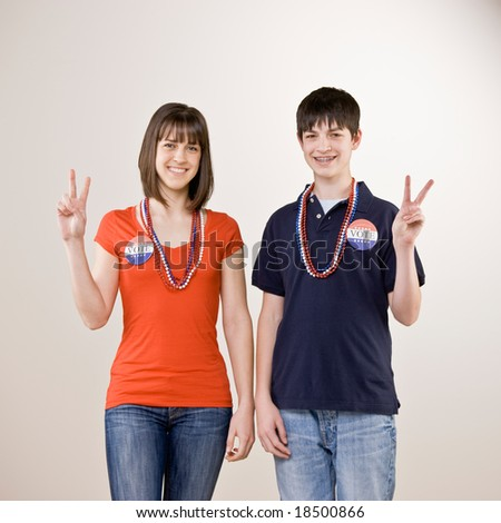 Patriotic teenagers with vote button and beads gesturing peace symbol - stock photo