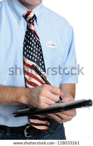 "Patriotic voter wearing a U.S. flag tie and dress shirt sporting an ""I voted"" sticker puts pen to pad to fill out form, poll, ballot or survey"