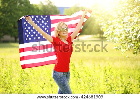 Patriotic young woman with American flag. Outdoor