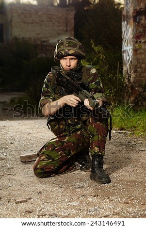 Patrolling soldier in camouflage battle uniform  - stock photo