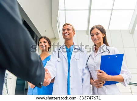 Patron. Senior male businessman shakes hands doctors in hospital - stock photo